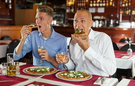 Two happy men emotionally watching sports on tv while eating pizza with white wine in cozy restaurant