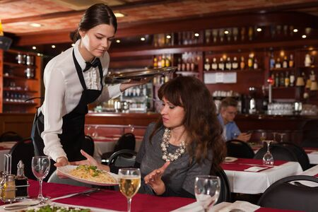 Female client expressing dissatisfaction with ordered dish served by young waitress in restaurant