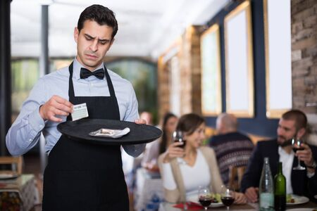 dissatisfied  male waiter keeps money for the order in the restaurant