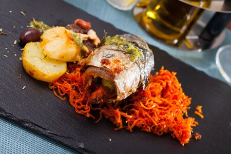 Delicious mackerel roll with bacon filling served with baked potato and grated carrot Stok Fotoğraf - 130028391