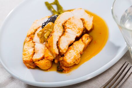 Tasty baked turkey breast with prunes, walnut and sauce on plate