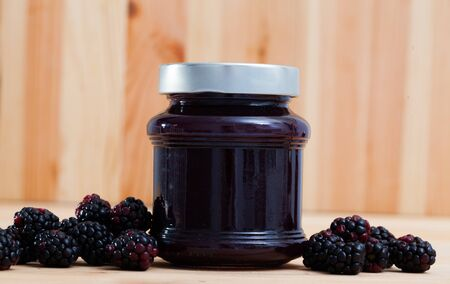 Tasty sweet homemade blackberry jam in closed glass jar and ripe berries on wooden surface