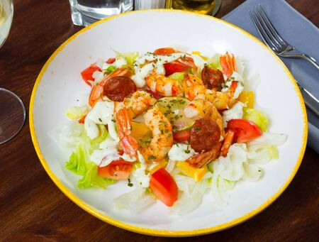 Tasty salad of roasted prawns and chorizo sausage with vegetable mix, sliced lemon and orange topped with creamy sauce