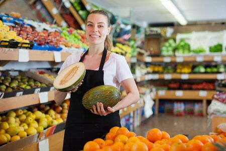 Young woman holding two fresh melon during offering fresh fruits on the store