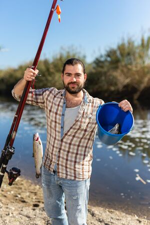Happy fisherman with caught fish on a hook and a fishing rod in his hands Banque d'images