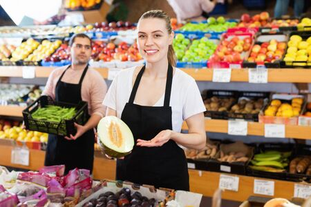 Young happy cheerful positive smiling female seller with half of melon and man on background having box of green beans on the supermarket Stock Photo