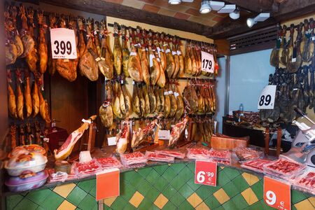 Assortment of traditional delicious appetizing  meat shop with dangling legs jamon and packings of sliced ham Stock Photo