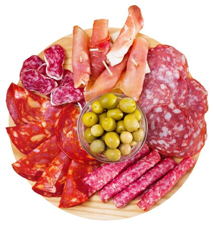 Top view of coldcuts of delicious Spanish cured jamon and piquant sausages garnished with green olives on wooden board. Isolated over white background Zdjęcie Seryjne