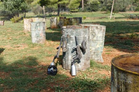 Black protective mask and marker guns lying on ground near old barrels with traces of paint on open paintball field