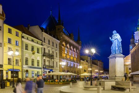 Illuminated streets of Torun with Town Hall and statue of Nicolaus Copernicus in evening