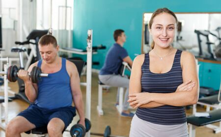 Cheerful girl in sportswear on background of exercising with dumbbells men in gym