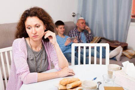 Porträt einer attraktiven verärgerten Frau, die zu Hause am Tisch im Hintergrund sitzt, mit ihrem Ehemann und ihrem Sohn im Teenageralter entspannt auf dem Sofa