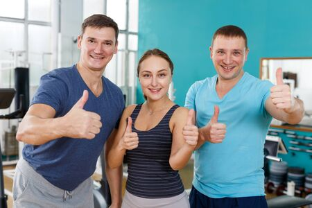 Portrait of cheerful sporty group of three posing at gym and showing thumb up Stockfoto