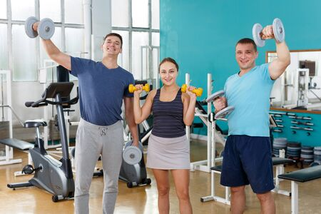Happy girl and two men posing with dumbbells and barbell in gym