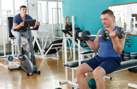 Portrait of man in sportswear lifting dumbbells at gym Stockfoto