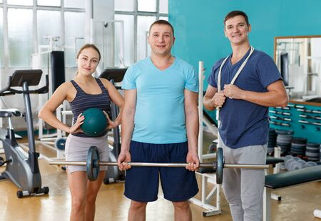Portrait of three smiling people holding sport equipment in gym Stockfoto