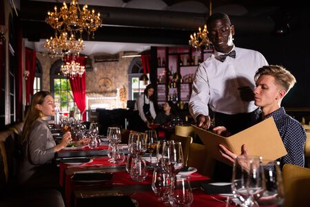 African-american waiter is taking order from client in fashionable restaurant