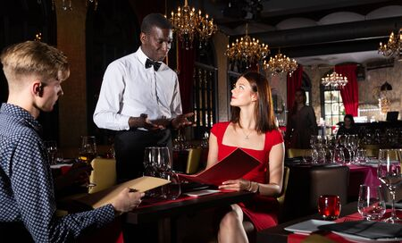 African-American waiter taking order from young couple of visitors at luxury restaurant Stockfoto