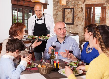 Cheerful waiter serving plates of salad to happy family having dinner at restaurant