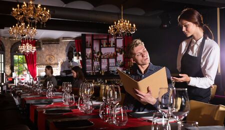 Portrait of handsome young man holding menu and ordering food in luxury restaurant Stockfoto