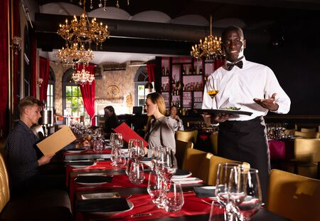 Hospitable african-american waiter standing with serving tray meeting restaurant guests Фото со стока