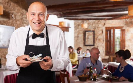 Portrait of happy waiter in white shirt and black apron holding good tips