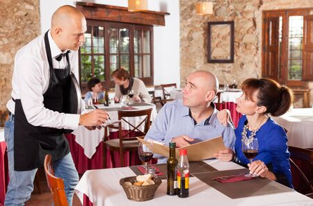 Happy couple having dinner in restaurant and making order