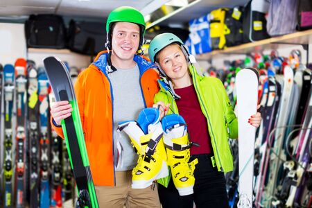 Glad customers are satisfied of their choice of ski and boots for skiing in sport shop