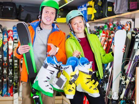 family are choosing ski in sport shop.