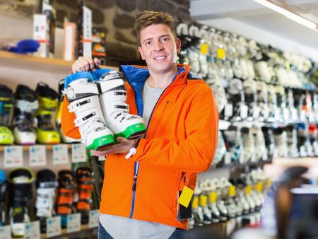 Smiling young male in ski equipment is demonstrating boots for skiing in store