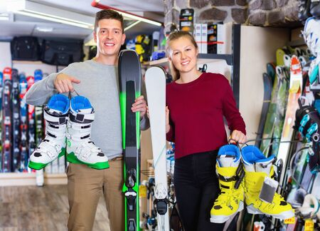 Happy  positive smiling woman and man are demonstrating their choice of ski boots