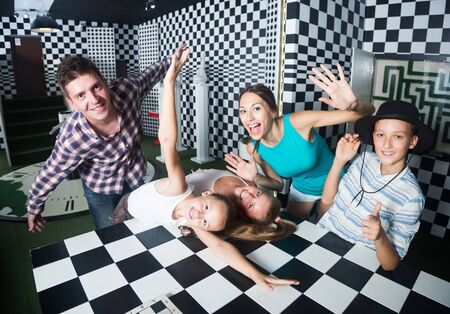 Ordinary family is visiting of escaperoom stylized under chessboard Foto de archivo - 129242404