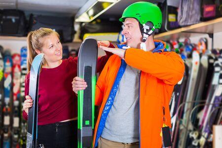 Seller woman is helping happy male in equipment to choose ski in sport shop. Stok Fotoğraf