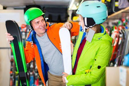 Happy family are choosing modern ski in sport store