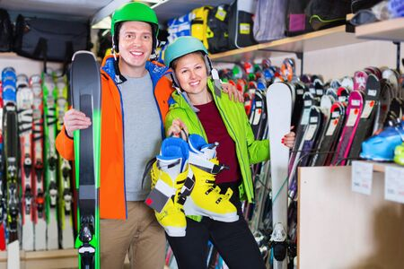 Cheerful positive smiling girl with boyfriend in equipment are demonstrating their choice of ski and boots in store.