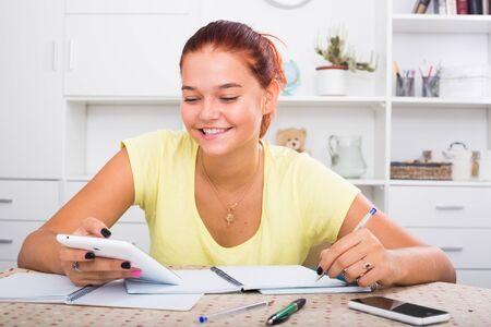 Chica adolescente positiva tomando notas mientras estudia en casa