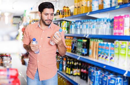 Adult man is consumering bottles with water in hypermarket.