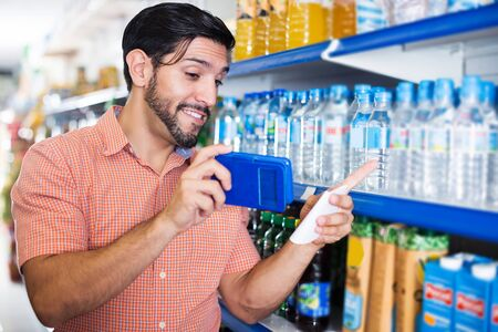 Adult man is choosing mineral water with help note list when talking phone with wife in market.