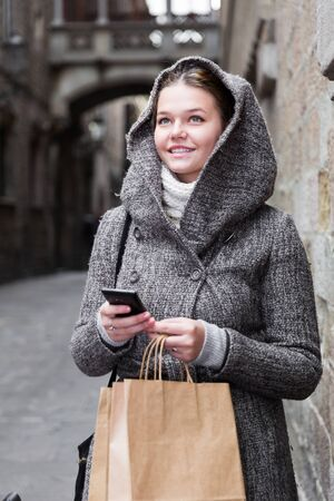 girl using mobile phone at the street in coat hood in autumn season