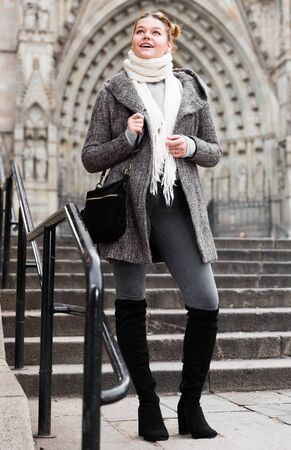 positive girl teenager in the historical city in scarf outdoors