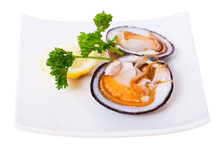 Fresh bivalve mussels (glycymeris) served with lemon on plate. Isolated over white background Stock fotó