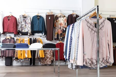 View of clothing boutique hall with many elegant clothes on hangers and shelfs