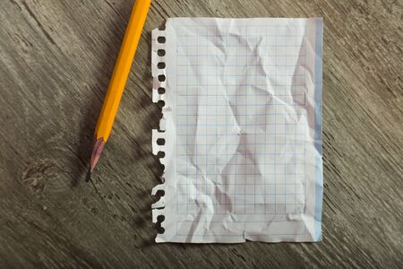 Crumpled notebook sheet in cage with pencil on table