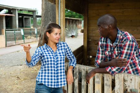 Irritated young woman and her husband emotionally talking near wooden fencing of stable