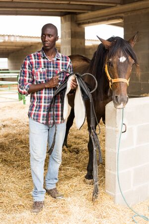 Young man farmer removes saddle from horse at  stable at farm outdoor
