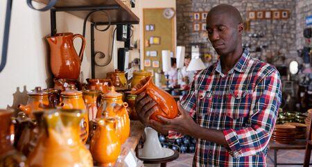 Portrait afro-ameciran man with ceramic tableware at shop