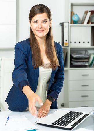 Smiling and confident young woman giving hand for handshaking Banque d'images - 129015485