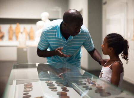 Afro father and his daughter looking at exhibits in glass stands at historical museum Reklamní fotografie
