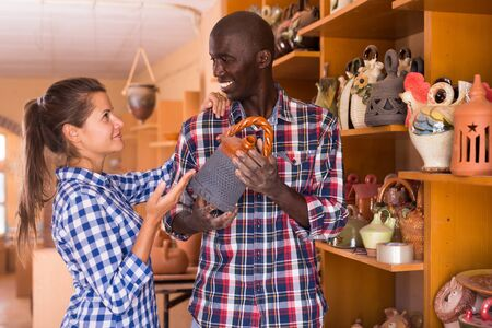 Portrait of couple choosing ceramic production in pottery shop