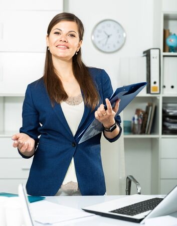 Young female office worker is standing with documents before signing it in office